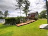 Honey-Harbour-Waterfront-Georgian-Bay-Luxury-Cabin-Facing-Single-Storey-Building-Side-With-Manicured-Lawn-Canadian-Shield-Garden-and-Deck-Walkway