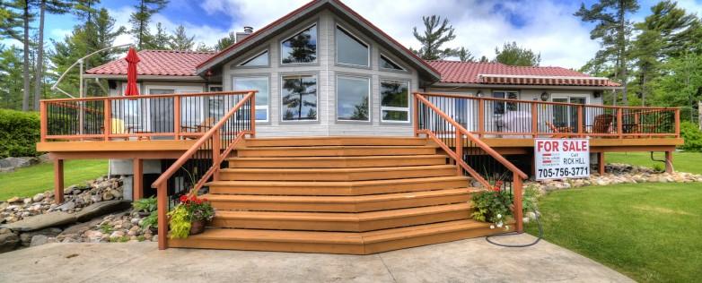 Georgian Bay Cottage For Sale In Honey Harbour: Facing Steps Up To Deck With Tall Single Storey Building