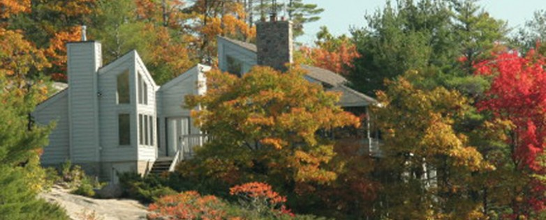 Honey-Harbour-Cottage-Georgian-Bay-Facing-Exterior-Two-Storey-Building-Façade-In-Trees-With-Autumn-Colours